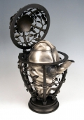 Metal tea kettle with fabric texture contained in floral cage