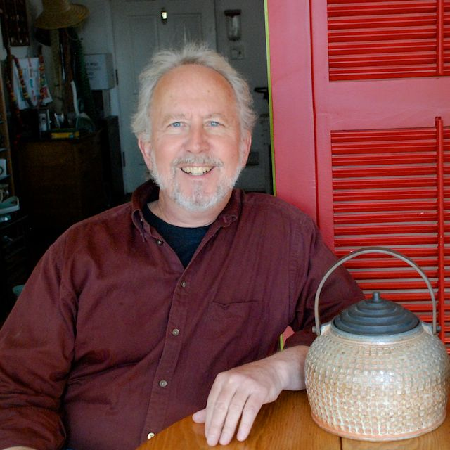 Richard Burkett sitting next to ceramic kettle