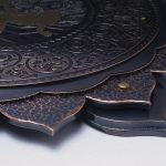 Metal flower with intricate floral designs embossed