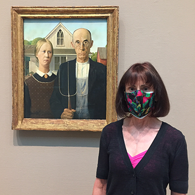 Woman posing in front of Grant Wood painting