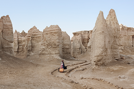 Woman with luggage in rocky desert