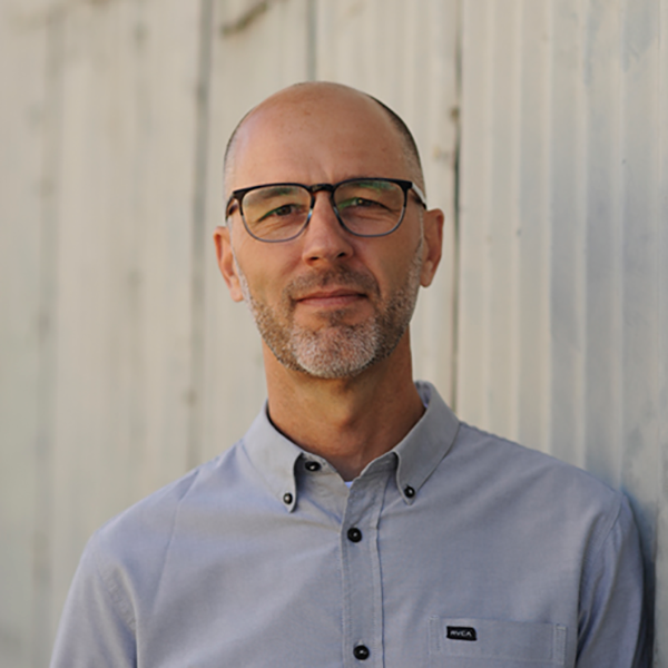 Man in grey collared shirt and glasses