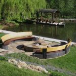 Outdoor fire pit on a lake with two semi-circular benches