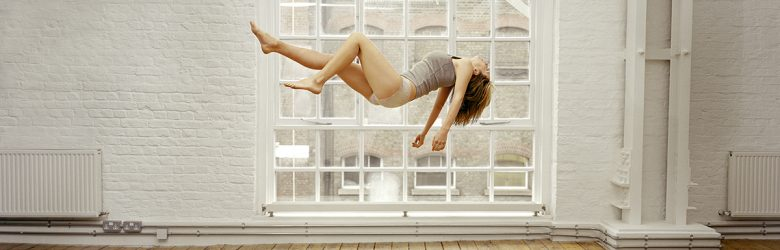 Female floating in an empty white room with wood floors