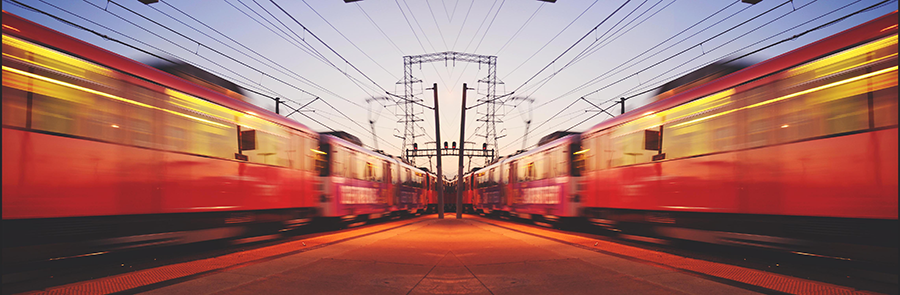 Red trolley cars receding to horizon on parallel tracks at sundown