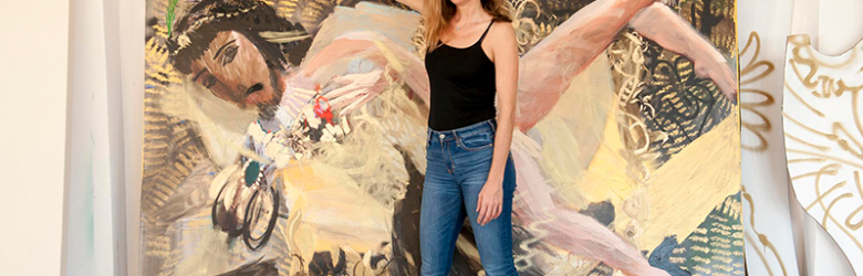 Artist Alida Cervantes in her studio touching a large painting