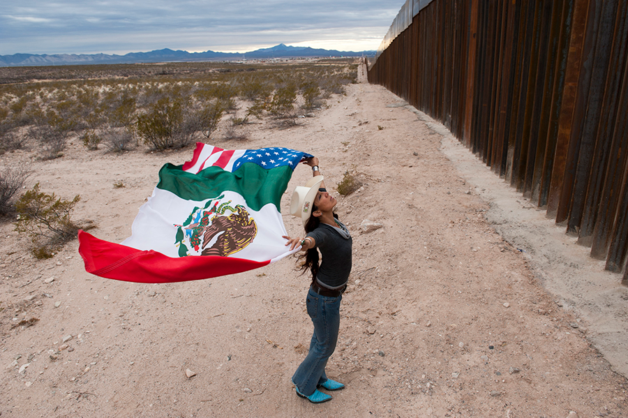 Woman at International border wall holding Flag